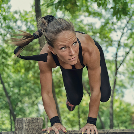 Athlète féminine de saut à travers obstacle en bois sur le sentier de remise en forme Banque d'images - 57152004