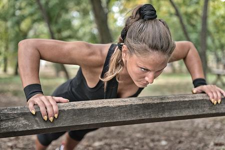 push ups: Female athlete doing push ups on wooden barrier Stock Photo