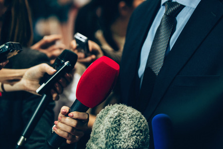 spokesperson: Journalists interviewing business person on public event. Toned image