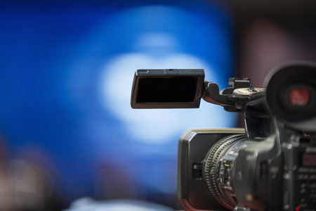 commercial event: Video camera at corporate presentation in a darkened conference hall. Focus set on camera, background blurred. Convenient copy space.