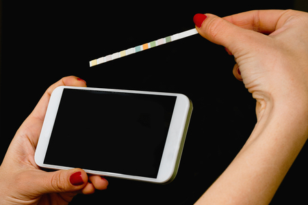 heathcare: Personal mobile heathcare app - Patient analyzing results with smart phone and indicator paper strip Stock Photo