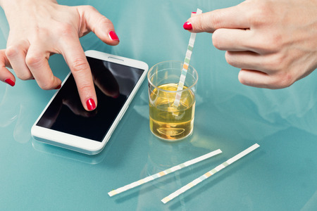 patient data: Personal urine testing kit - patient using urine test strips, entering data into smart phone app
