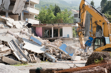 demolishing: Heavy construction machines demolishing residential building Stock Photo