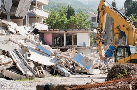 demolishing: Heavy construction machines demolishing residential building Stock Photo
