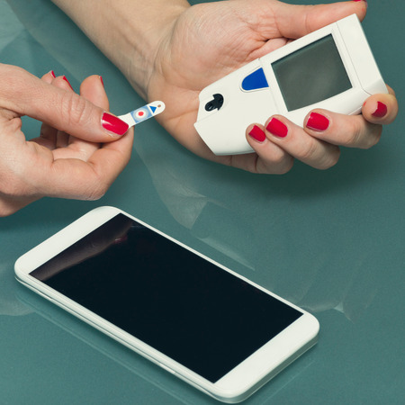 blood glucose meter: Personal blood sugar test with blood glucose meter and smart phone. Diabetes patient checking glucose levels, using smart phone to keep track of it. Blood sugar meter, smart phone, test strip, hand