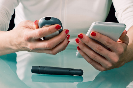 blood glucose: Blood Glucose Meter and Smart Phone Stock Photo