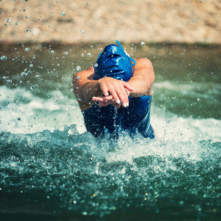 swimming cap: Action shot of a female triathlete at the moment of water entry. Shallow depth of field, blurred shore in the background. High speed used to capture water splash. She is wearing blue swimming cap and swimming suit.