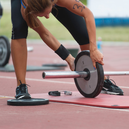 competitor: Female CrossFit competitor changing weights on weightlifting bar Stock Photo