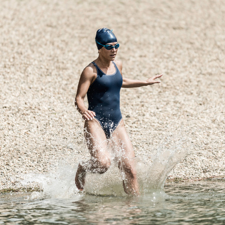 xxxl: Triathlon - Muscular female athlete running into the water. She is wearing matching blue swimming cap, swimming goggles and one-piece swimsuit. Detailed high speed action shot. Model released, color graded, XXXL DSLR image taken with Nikon D800. Convenien