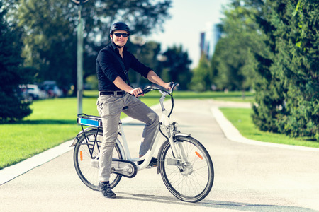 Young man with electric bicycle or E-bike Standard-Bild