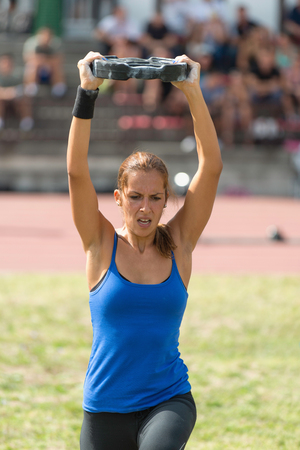 competitor: Female crossfit competitor doing walking weight plate lunges