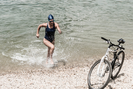 triathlete: Triathlete exercising, coming out of the water towards her bicycle