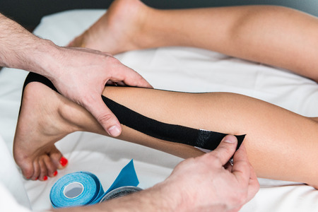 taping: Therapist placing kinesio taping on foot