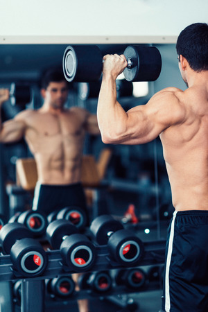 only the biceps: Body building champion exercising in the gym, standing on front of the mirror