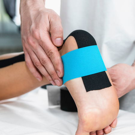 taping: Physical therapist placing taping on patients foot Stock Photo
