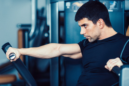 only one mid adult male: Muscular young man exercising on rowing machine in modern gym. Toned image
