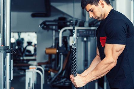 현대 체육관에서 새로운 운동 기계에 근육 남성 선수의 DSLR 사진. 모델은 경쟁을 준비하는 신체 구축 챔피언입니다. 모델 검은 체육관 운동 복장을 입