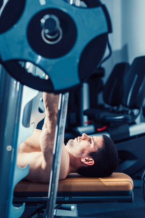only one mid adult male: Muscular man lifting weights, lying on weight bench in gym. Toned image Stock Photo