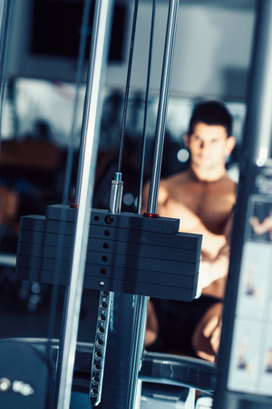 only one mid adult male: Muscular young man exercising on rowing machine in modern gym. Focus set moving machine weights, model and gym blurred. Tilted, toned image