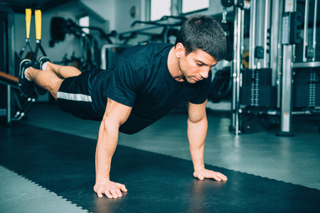 only one mid adult male: Man exercising with TRX bands, doing push-ups with legs suspended.