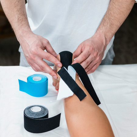 tarsus: Placing kinesio tape on patients foot Stock Photo