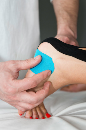 tarsus: Therapist positioning kinesio taping on patients foot