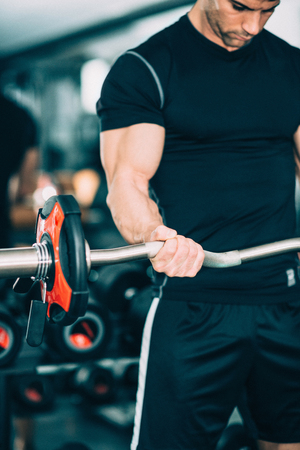 only the biceps: Young man exercising in gym with barbell weights