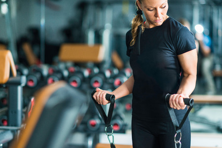 body built: Female athlete exercising in the gym, using TRX resistance bands. Model is wearing black contemporary sportswear. Floodlit from back.Shallow depth of field technique is keeping only model in focus while leaving gym softly blurred . Image is color graded a