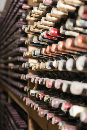 identifying: Assortment of old wine bottles in a cellar. Selective focus, mold and dust visible, all identifying marks removed Stock Photo