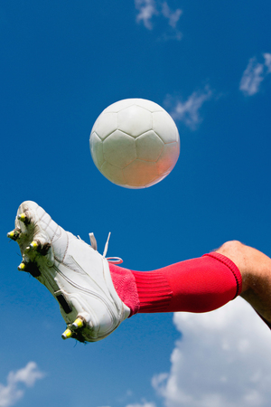 football cleats: Soccer player kicking the ball