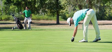 Golfer and caddy on putting green 版權商用圖片