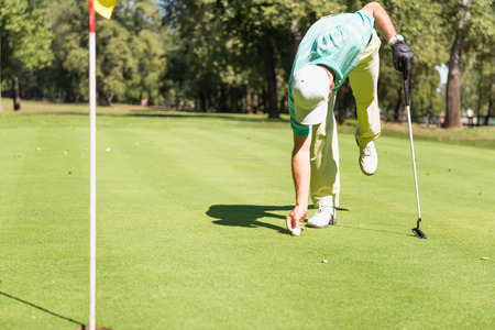 by placing: Golfer placing marker behind the ball Stock Photo