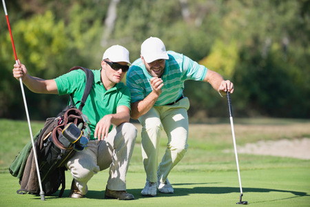 only mid adult men: Golfer and Caddy contemplating a putting shot Stock Photo