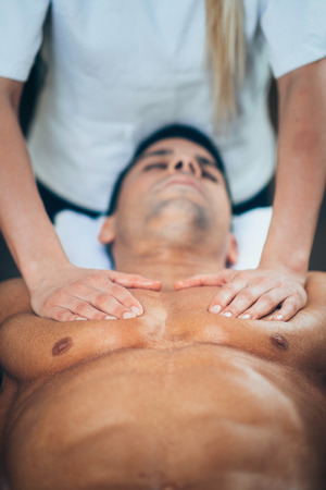 masaje deportivo: Sports massage - Chest massage - Physical therapist doing massage of chest. Toned image, selective focus set on chest and hands.