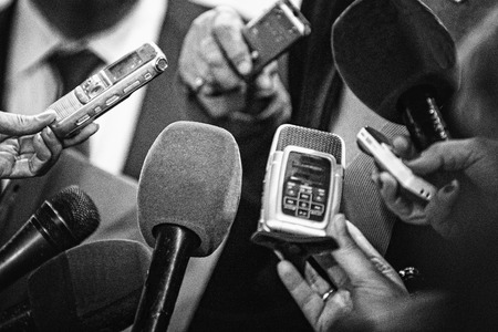 Journalists with recording equipment flocking around important people. Black and white retro style processing 版權商用圖片