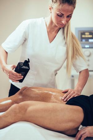 toned image: Sports massage - Female physical therapist massaging man, applying massage oil. Toned image