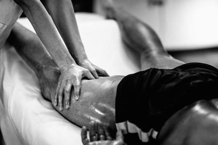 Sports massage - Leg massage - Physical therapist doing massage of legs, applying strong finger pressure. Black and white photo, selective focus. Stock Photo