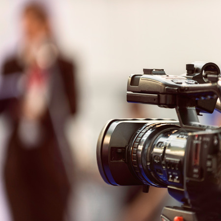 commercial event: Public relations - PR manager talking to media at press conference. Camera in focus, spokesperson blurred Stock Photo