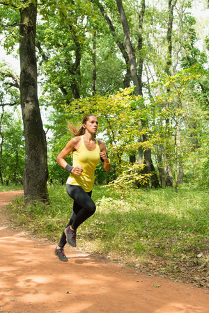 vertical wellness: Young woman jogging in park