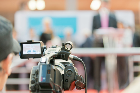 television camera: Television camera recording an important event. Camera in focus, cameraman and spokesperson blurred Stock Photo