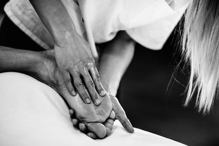masaje deportivo: El masaje deportivo - Masaje de pies - haciendo terapeuta f�sica de los pies de los hombres. foto blanco y negro, enfoque selectivo.