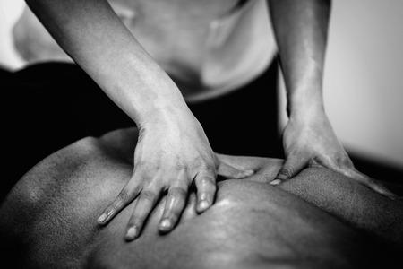 masaje deportivo: Sports massage - Lower back massage - Physical therapist doing massage of lower back. Black and white photo, selective focus.