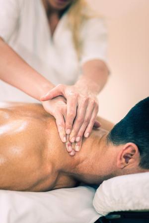 collo: Massaggio sportivo - Massaggio del collo - Fisioterapista facendo massaggio del collo. Viraggio, set messa a fuoco selettiva sul petto e le mani. Archivio Fotografico