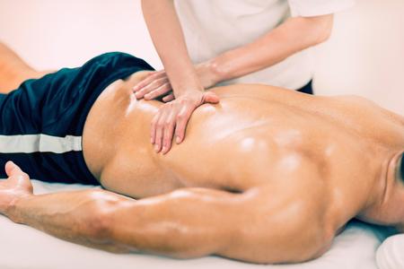 sports massage: El masaje deportivo - Baja de la espalda masaje - terapeuta f�sico hace el masaje de espalda baja. Tonos de imagen, enfoque selectivo. Foto de archivo