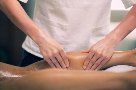 leg massage: Sports massage - Leg massage - Physical therapist doing massage of calfs, applying strong finger pressure. Toned image, selective focus.