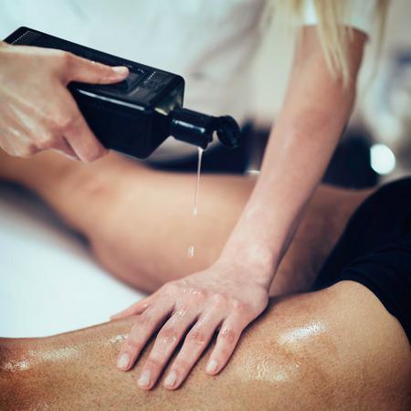 toned image: Sports massage - Masseuse using massage oil. Toned image, selective focus Stock Photo