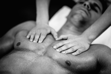 Sports massage - Chest massage - Physical therapist doing massage of mens chest. Black and white photo, selective focus. Stock Photo