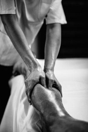 스포츠 마사지 - 송아지 마사지 - calfs의 마사지를하고 물리 치료사, 강력한 손가락의 압력을 적용. 흑백 사진, 선택적 포커스. 스톡 콘텐츠