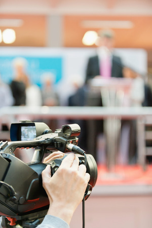 commercial event: Press conference. Camera in focus, blurred spokesman in the background