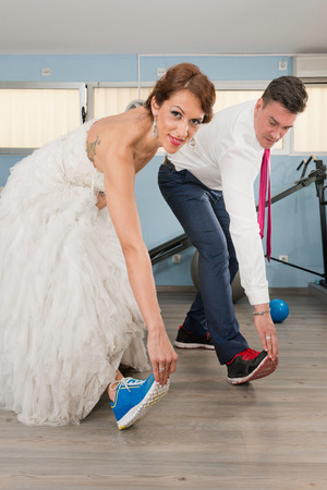 gym dress: Young couple getting fit for their wedding day. Concept with couple in wedding dress and suit in a gym.